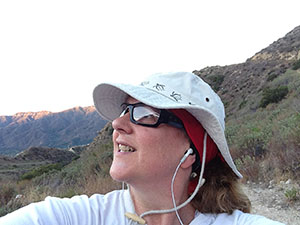 Laurie gazes out at the sky while hiking in the mountains at dawn